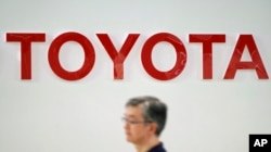 A visitor walks through a Toyota showroom in Tokyo, Aug. 3, 2018.