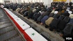 Warga Suriah yang berkabung melakukan shalat jenazah terhadap 11 orang polisi yang menjadi korban pemboman hari Jumat di Damaskus (7/1).