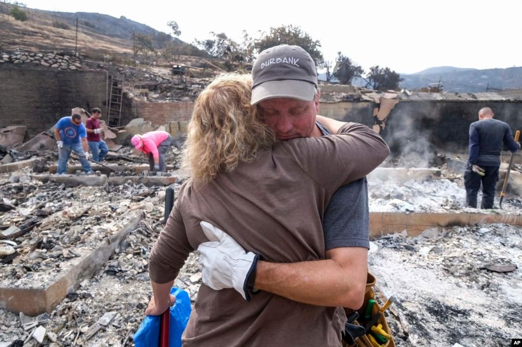 로스앤젤레스 선랜드-터헝가 지역 주민 크레이그 볼리슨이 타버린 집터에서 친구와 포옹하고 있다. 9월들어 섭씨 40도를 웃도는 폭염이 다시 시작된 미국 서부지역 일대에 대규모 산불이 번지면서 수많은 주민들에 소개령이 내렸다.
