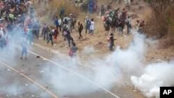 Honduran migrants hurl stones at Guatemalan soldiers amid tear gas in Vado Hondo, Guatemala, Sunday, Jan. 17, 2021.
