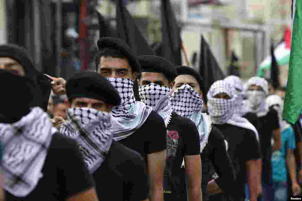 Palestinians wearing traditional headscarves and carrying black flags attend a demonstration calling for an end to the Israeli offensive in the Gaza Strip after Eid al-Fitr prayers, at Al-Baqaa Palestinian refugee camp, near Amman, Jordan, July 28, 2014.