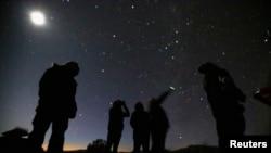 امریکی ریاست سیڈورا کے علاقے میں لوگ رات کے وقت آسمان پر ایک چمکتی ہوئی پراسرار چیز کا مشاہدہ کر رہے ہیں۔ فائل فوٹو