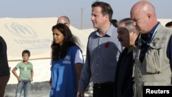 Britain's PMr David Cameron walks with Jordanian Foreign Minister Nasser Judeh and UNHCR representative to Jordan Andrew Harper during his visit to Al-Zaatri refugee camp in the Jordanian city of Mafraq, November 7, 2012.