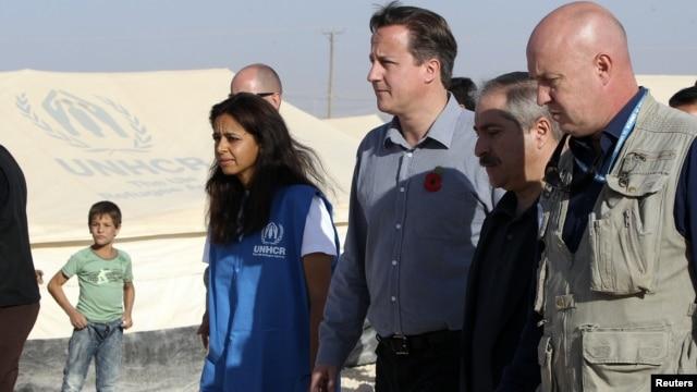 Britain's PMr David Cameron walks with Jordanian Foreign Minister Nasser Judeh and UNHCR representative to Jordan Andrew Harper during his visit to Al-Zaatri refugee camp in the Jordanian city of Mafraq, November 7, 2012.