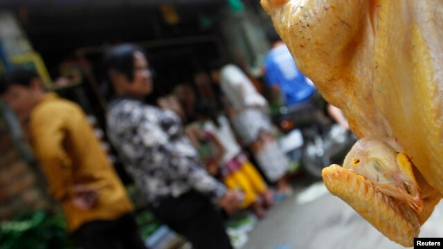 FILE - A chicken is displayed for sale at a market in Phnom Penh.