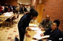 Sebastian Snelling, left, is given instructions on using a paper ballot as the precinct switched over from electronic voting machines after a judge ordered the location to stay open until 10 p.m., in Atlanta, Nov. 6, 2018.