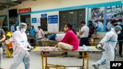 Na fotografiji snimljenoj 23. aprila 2021. bolničko osoblje prevozi pacijenta s Covid-19 koronavirusom u bolnički kompleks u New Delhiju. (Foto Maude BRULARD / AFP)