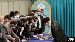 Pemimpin Tertinggi Iran Ayatollah Ali Khamenei disambut oleh pekerja pemilihan, semuanya mengenakan masker wajah karena pandemi COVID-19, saat ia tiba untuk memberikan suaranya pada 18 Juni 2021. (Foto: AFP)