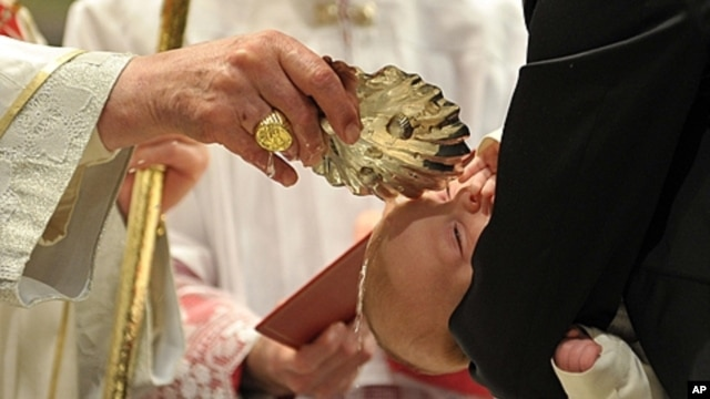 Pope Benedict XVI baptizes one of 21 newborns during in the Sistine Chapel, the Vatican, Jan. 9, 2011 (file photo).