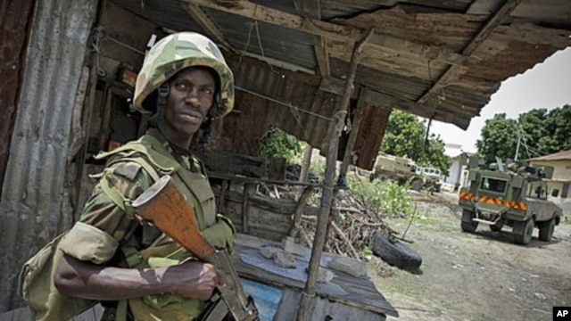 A Ugandan soldier serving with the African Union Mission in Somalia stands guard during the removal of a haul of 155mm artillery shells that were found in a house deep inside a former Al Shabab stronghold in the Somali capital Mogadishu, August 12, 2011