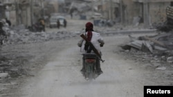 A man drives a motorcycle while carrying his weapon near damaged buildings in the northern Syrian town of al-Bab, Syria, March 1, 2017.