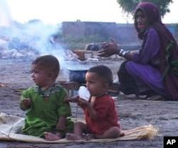 سندھ میں سیلاب سے متاثرہ خاتون بچوں کے لیے کھانا تیار کررہی ہے