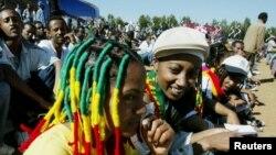 """Des jeunes filles coiffées de """"locks"""" aux couleurs de rasta assises a la place Meskel a Addis Abeba, Ethiopie, 6 février 2005."""