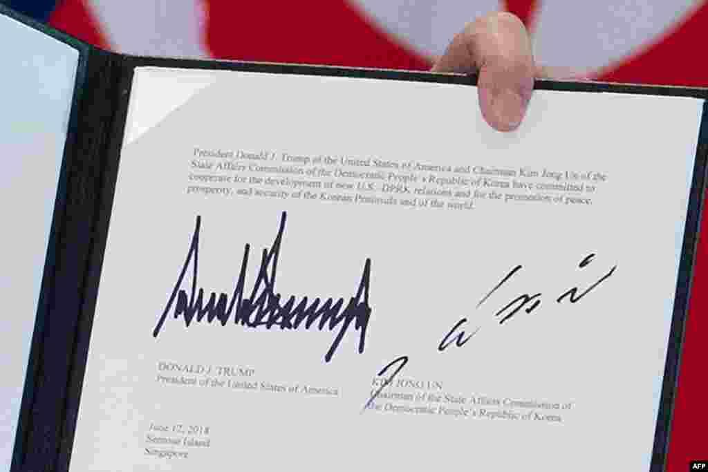 도널드 트럼프 미국 대통령이 자신과 김정은 북한 국무위원장이 서명한 미북 정상회담 공동성명을 들어보이고 있다.