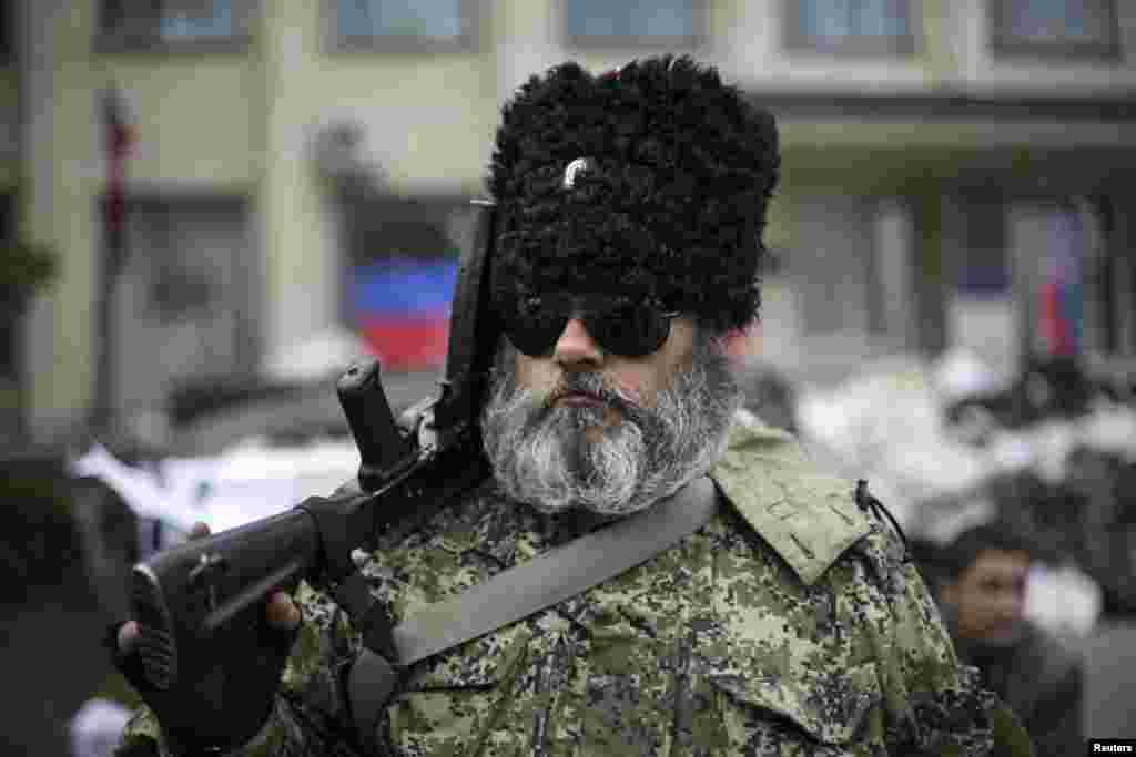 A pro-Russian armed man stands guard outside a regional government building seized by the pro-Russians, in Kramatorsk, eastern Ukraine, April 22, 2014.