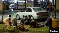 Manifestantes se cubren de los disparos en Ferguson, Missouri, durante los eventos de la noche del domingo.
