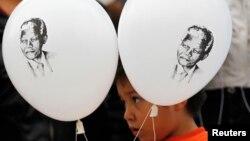 小孩手持印有曼德拉肖像的气球