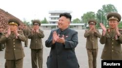 Pemimpin Korea Utara Kim Jong Un bertepuk tangan dalam sesi foto dengan tentara.