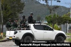 Tentara dan polisi duduk di atas mobil saat berpatroli di Wamena, Papua, 9 Oktober 2019. (Foto: Antara/M.Risyal Hidayat via REUTERS)