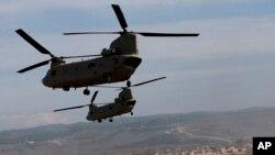 ເຮລີຄັອບເຕີ ສະຫະລັດ U.S. CH-47 Chinooks ບິນຜ່ານເຂດຊ້ອມຮົບຈຳລອງໃນລະຫວ່າງການຝຶກຊ້ອມທະຫານ NATO ໃນເມືອງ Zaragoza, ສເປນ, 4 ພະຈິກ, 2015.