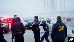FILE - A California Highway Patrol officer detains a protester on the San Francisco-Oakland Bay Bridge, Jan. 18, 2016, in San Francisco. A group of demonstrators from the group Black Lives Matter caused a shutdown of one side of the bridge in a police brutality protest.