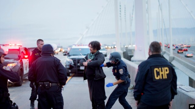 FILE - A California Highway Patrol officer detains a protester on the San Francisco-Oakland Bay Bridge, Jan. 18, 2016, in San Francisco.
