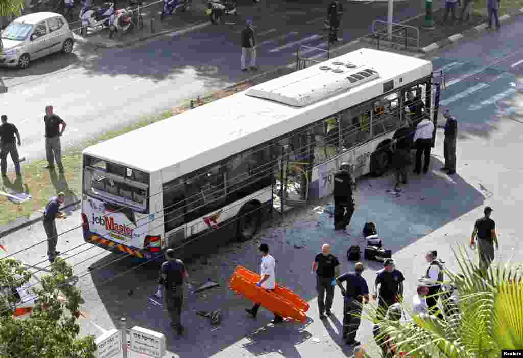 Israeli police explosives experts survey a damaged bus at the scene of an explosion in Tel Aviv November 21