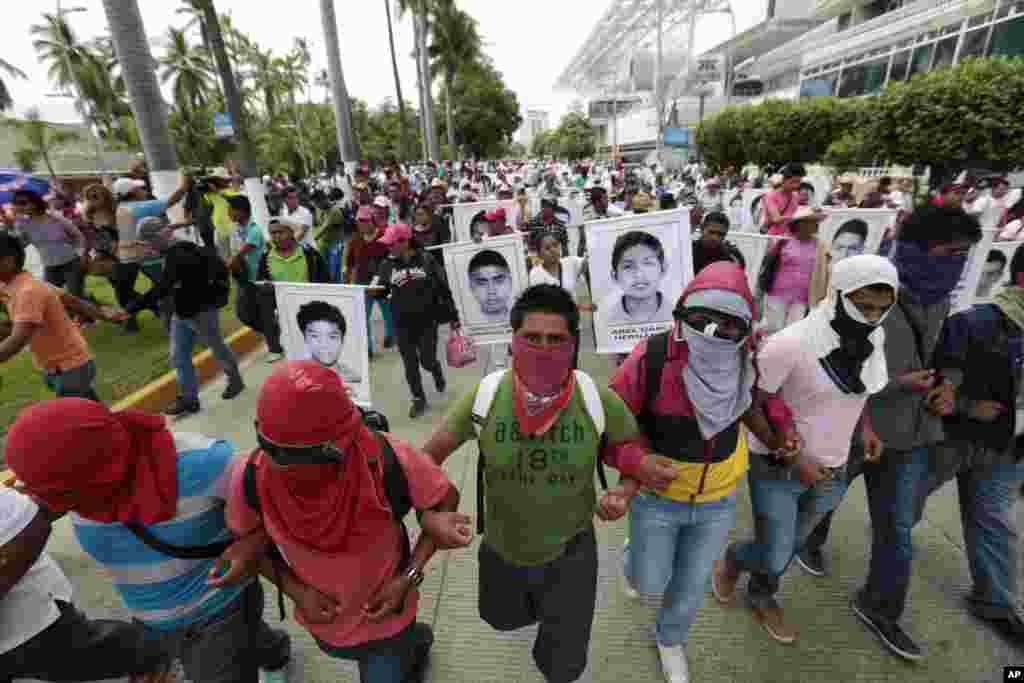 Người biểu tình tuần hành và hô khẩu hiệu với hình ảnh của những sinh viên mất tích trong cuộc biểu tình vụ 43 sinh viên trường đại học sư phạm Isidro Burgos mất tích ở thành phố Acapulco, bang Guerrero, Mexico.