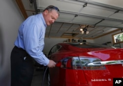Jeff Solie plugs in his electric Tesla sedan at his home, in New Berlin, Wis., July 13, 2017. Electric cars are seeing growing support around the world. But there's a problem: There aren't enough places to plug those cars in.