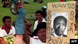 Un sympathisant du Congrès national africain (ANC) tient une affiche anti-président Lucas Mangope et une jambe de mannequin lors d'un rassemblement à Mmabatho le 13 mars 1995.