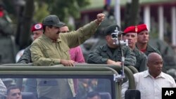 FILE - Defense Minister Vladimir Padrino Lopez, center right, face obscured, and Gen. Ivan Hernández, standing behind Padrino Lopez, head of both the presidential guard and military counterintelligence, accompany Venezuela's President Nicolas Maduro as th