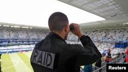 Polisi Perancis mengamati penonton di dalam stadion Bordeaux, tempat tim Belgia bertanding melawan Irlandia dalam kompetisi sepakbola Euro 2010 (18/6). (Reuters/Regis Duvignau)