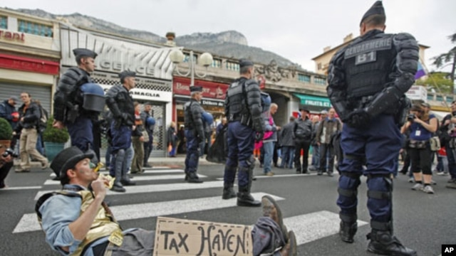 French gendarmes stand near an anti G20 demonstrator who takes part in protest against globalization and tax havens, at the French-Monaco border in Cap d'Ail, southeastern France, November 3, 2011.