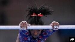 Simone Biles, de Estados Unidos, se ejercita en las barras asimétricas durante las calificaciones de gimnasia artística femenina en los Juegos Olímpicos de Tokio, el 25 de julio de 2021, en Tokio.