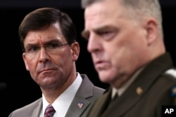 Defense Secretary Mark Esper, left, listens as Chairman of the Joint Chiefs of Staff Army Gen. Mark Milley, right, speaks during a briefing at the Pentagon in Washington, March 2, 2020.
