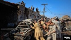 Warga setempat mengelilingi mobil yang hancur akibat ledakan bom, Rabu (2/2) di Peshawar.