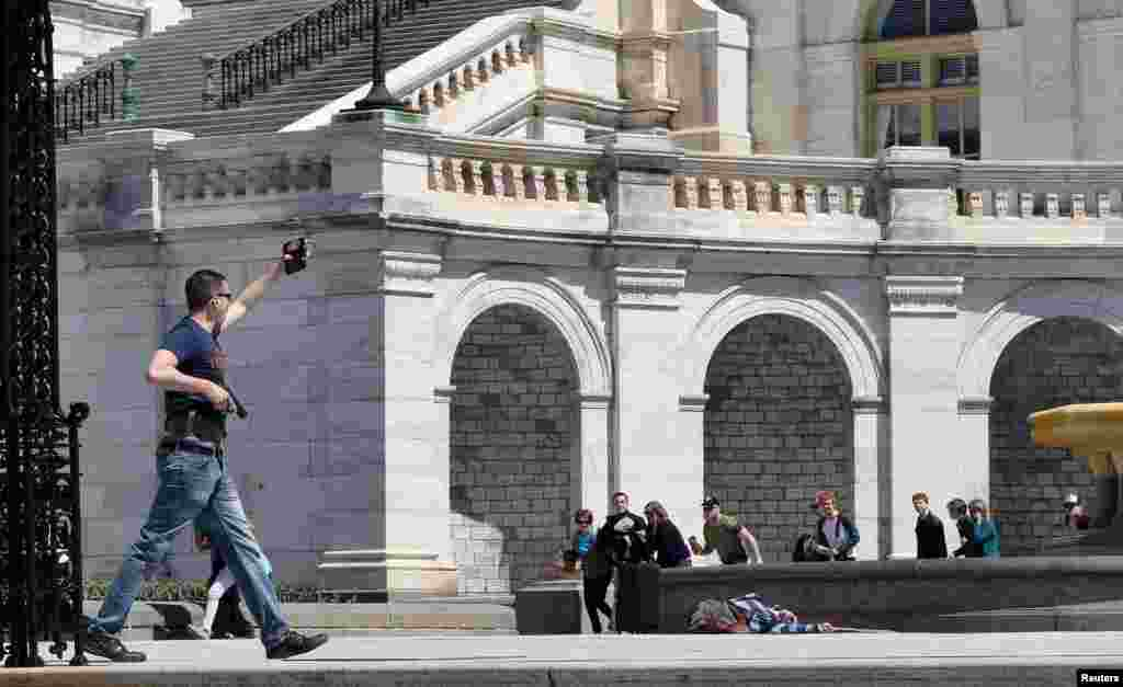 In this photo released today, a policeman shows his badge to tourists while approaching a man who had just shot himself in front of the Capitol in Washington D.C., April 11, 2015. A man shot himself dead near the U.S. Capitol, police said, sparking a temporary security lockdown at the complex on one of the busiest days for tourists in Washington.