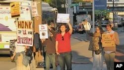 """參加""""佔領巴爾的摩""""的美國民眾在街頭手持標語"""