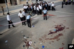 Israeli police officers inspect the scene of a stabbing attack in Beit Shemesh, central Israel, Oct. 22, 2015. Police say two Palestinians stabbed an Israeli man in the city of Beit Shemesh after attempting to board a bus ferrying children to school.