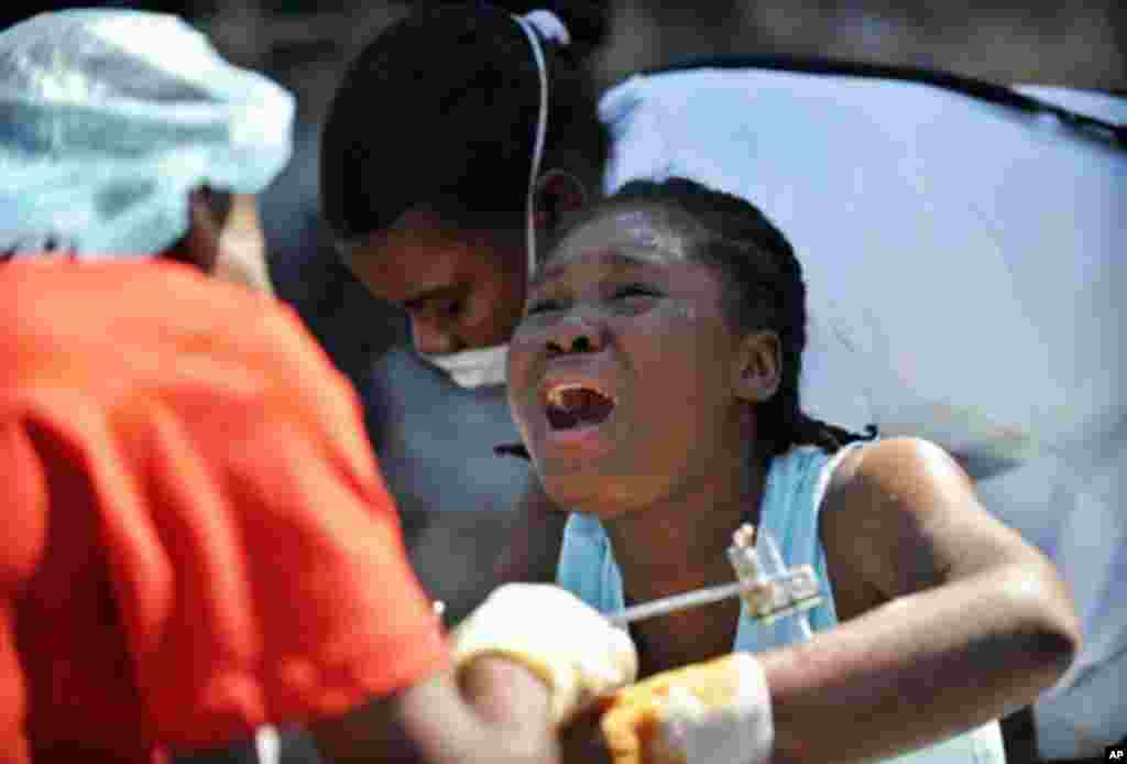 An injured woman cries in pain as she is treated at a makeshift hospital in Port-au-Prince, 21 Jan 2010 - AFP Photo