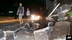 14일 일본 남부 규슈 구마모토 현에서 강진이 발생한 후, 주민들이 붕괴된 건물 터를 바라보고 있다.