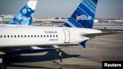 在纽约肯尼迪机场,一名工人正在给捷蓝航空公司飞机加油(资料图片)