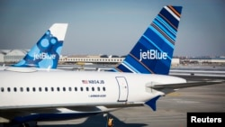 FILE - An airport worker fuels a JetBlue plane on the tarmac of the John F. Kennedy International Airport.
