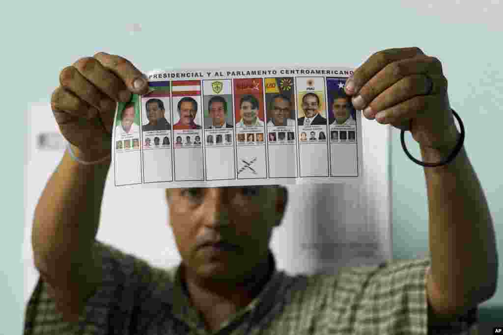 An election official shows a ballot marked for Free Party presidential candidate Xiomara Castro during the manual counting of votes after polls closed in Tegucigalpa, Honduras, Nov. 24, 2013.