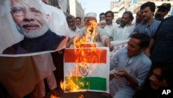 Pakistanis burn a representation of an Indian flag and a poster of Indian Prime Minster Narendra Modi during a protest to express support and solidarity with Indian Kashmiri people