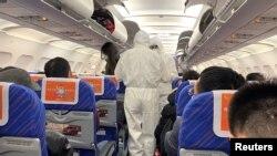 防疫人员1月25日身穿防护服在一架从长沙抵达上海的航班上进行筛查