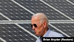 Joe Biden, yang saat itu masih kandidat presiden, berjalan melintas panel surya saat mengunjungi Insitiatif Energi Terbarukan Kawasan Plymouth, di New Hampshire, 4 Juni 2019. (Foto: Brian Snyder/Reuters)