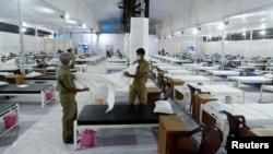 印度工人在孟买新近为新冠病毒感染者修建的隔离设施里为病人准备床铺。(2020年6月22日)