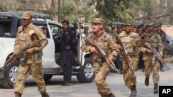 Tentara Pakistan bergegas menuju lokasi ledakan bom di Peshawar, Pakistan (18/2). Seorang militan menyamar sebagai polisi dan mengenakan jaket untukmeledakkan bom saat menyerang kantor seorang pejabat politik senior Pakistan. (AP Photo/Mohammad Sajjad)