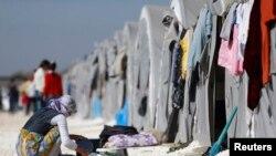一名从叙利亚科巴尼出逃的库尔德女难民在土耳其边境城镇叙吕奇的难民营内刷洗锅碗。(2014年11月11日)